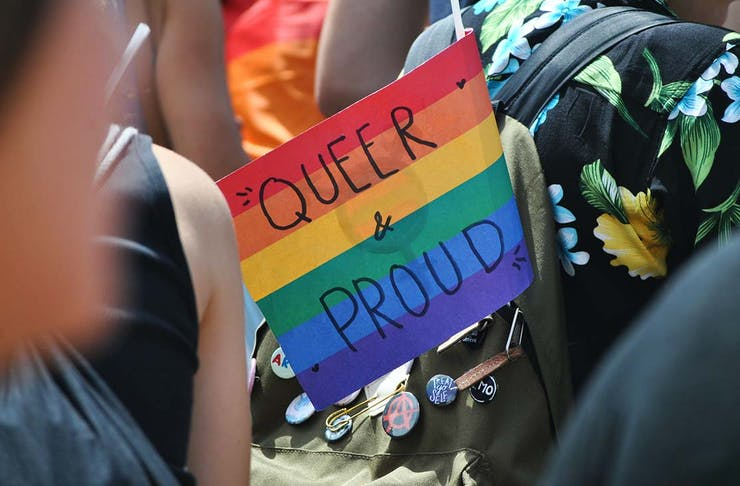 a rainbow flag with the text 'queer and proud'