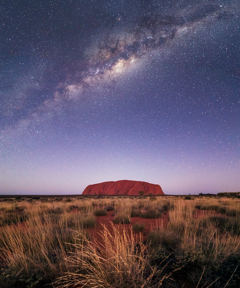 a sparkling night sky, full of stars, over the top of Uluru.