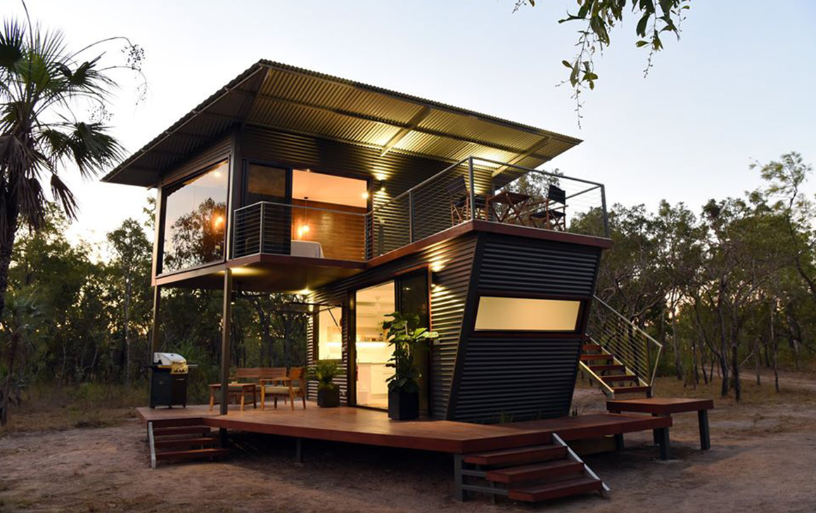 a two storey renovated shipping container is nestled in the bush.