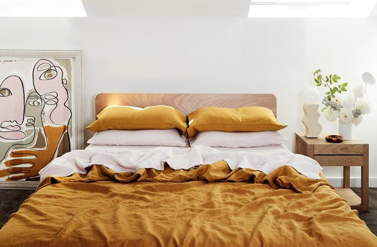a double bed, with mustard coloured sheets and pillows. a framed piece of art sits next to the bed.