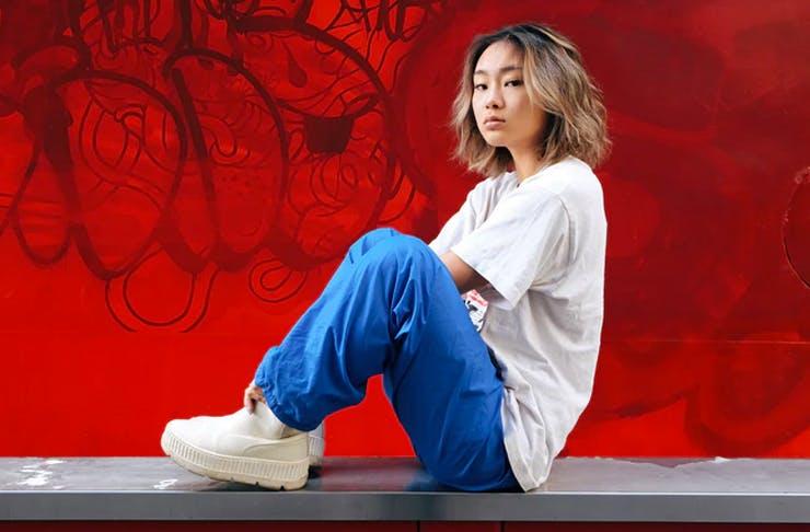 girl in streetwear sitting on wall in front of graffiti wall