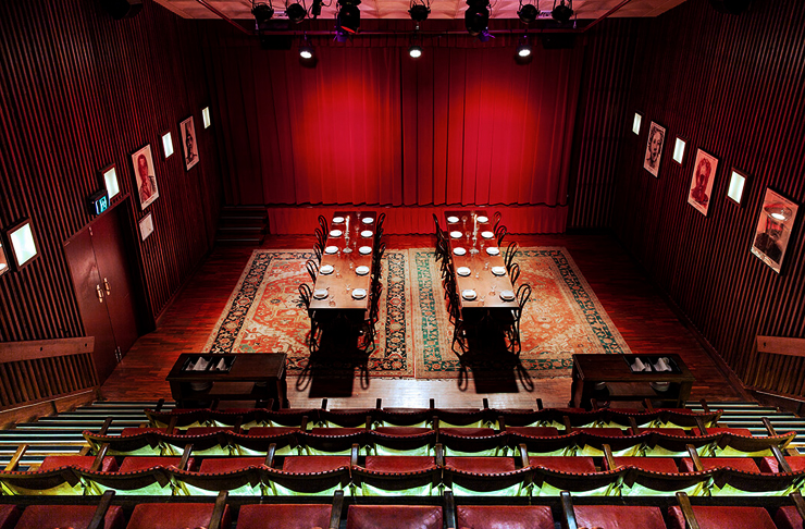interior of underground cinema with long dinner tables