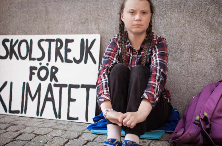 greta thunberg in raincoat protesting outside swedish parliament for climate change