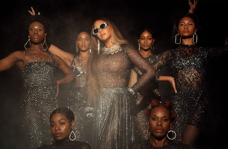 Beyonce on the set of Black Is King wearing big sunglasses and surrounded by a group of dancers.