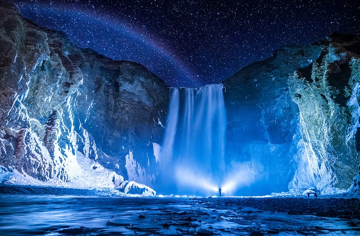 a person stands in front of the stunning Skógafoss, Iceland at night.