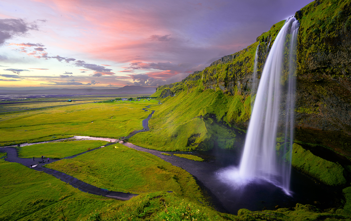 A stunning waterfall cascade down a bright green hill, with a dusty pink sunset in the background.