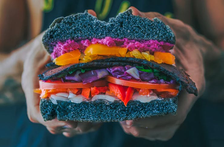 two hand hold a loaded vegan sandwich