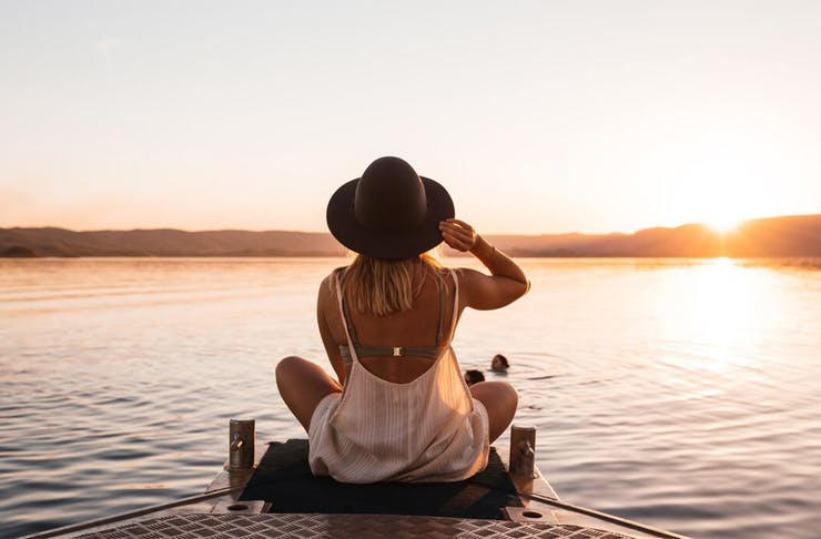 a woman sits on a poonton overlooking a lake in the kimberly region