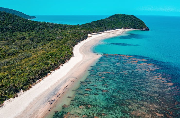 a strip of white sand beach fringed by lush rainforest and blue ocean.