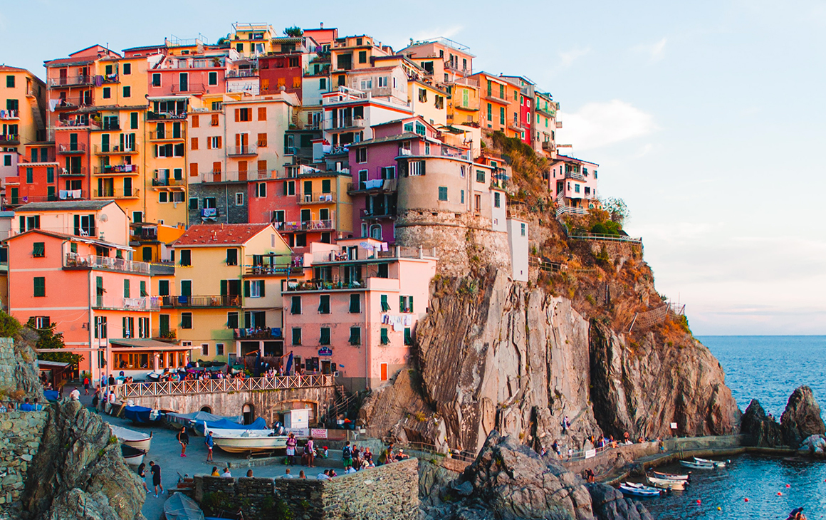 A cliffside is covered in colourful buildings on the edge of the Italian coast.