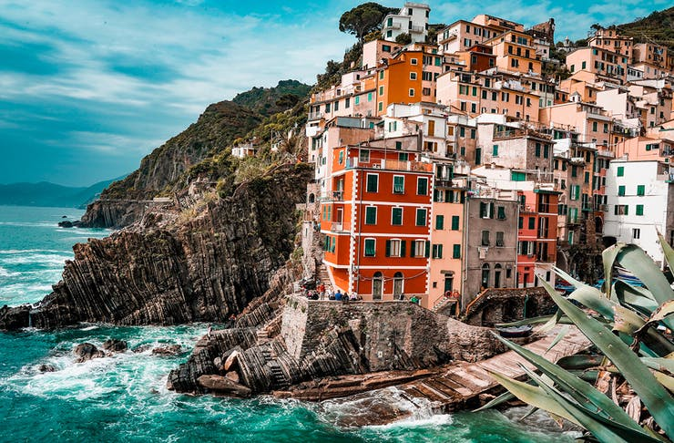 clusters of colourful building perch on the edge of a rugged coastline in Italy.
