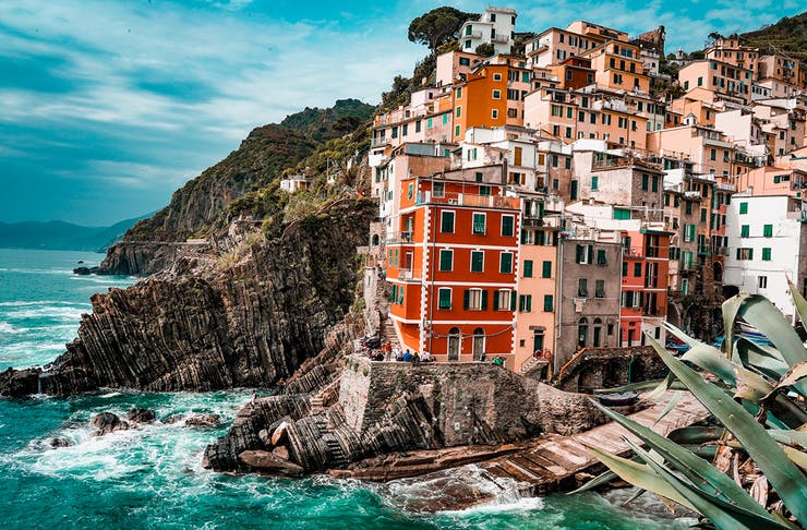 A cluster of colour buildings hug a rugged coastline in Italy