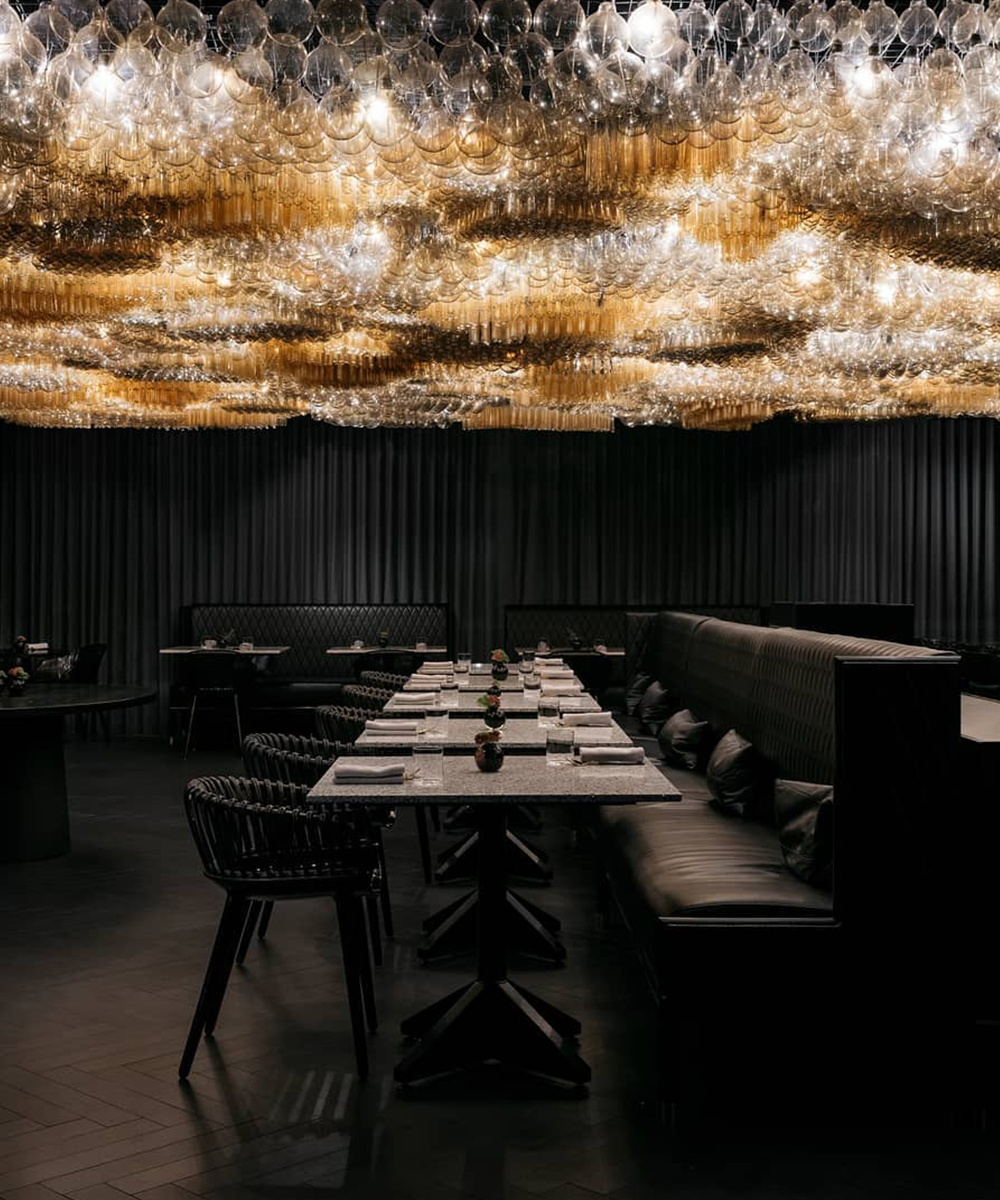 a cluster of stunning lights above an all black dining room