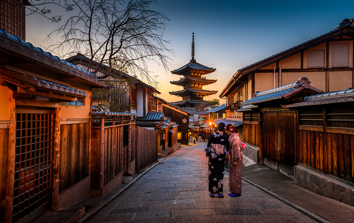 a stunning scene of Kyoto at dusk. the quiet street is lined with traditional buildings while two geisha women talk.