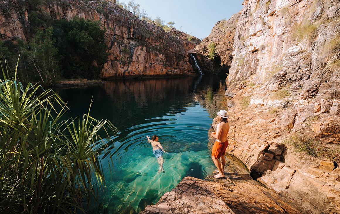 people swim in sparkling blue waters at Kakadu