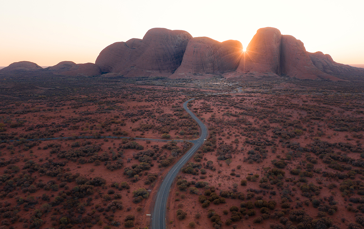 a winding road leads to the stunning red domes of Kata Tjuta. The sun peaking through the middle.
