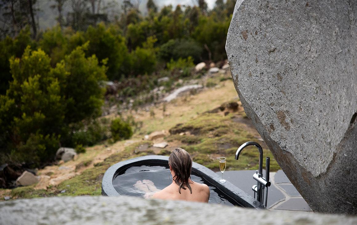 a woman bathes in a stone outdoor bath.