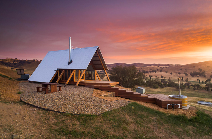 small eco hut on top of hill at sunset