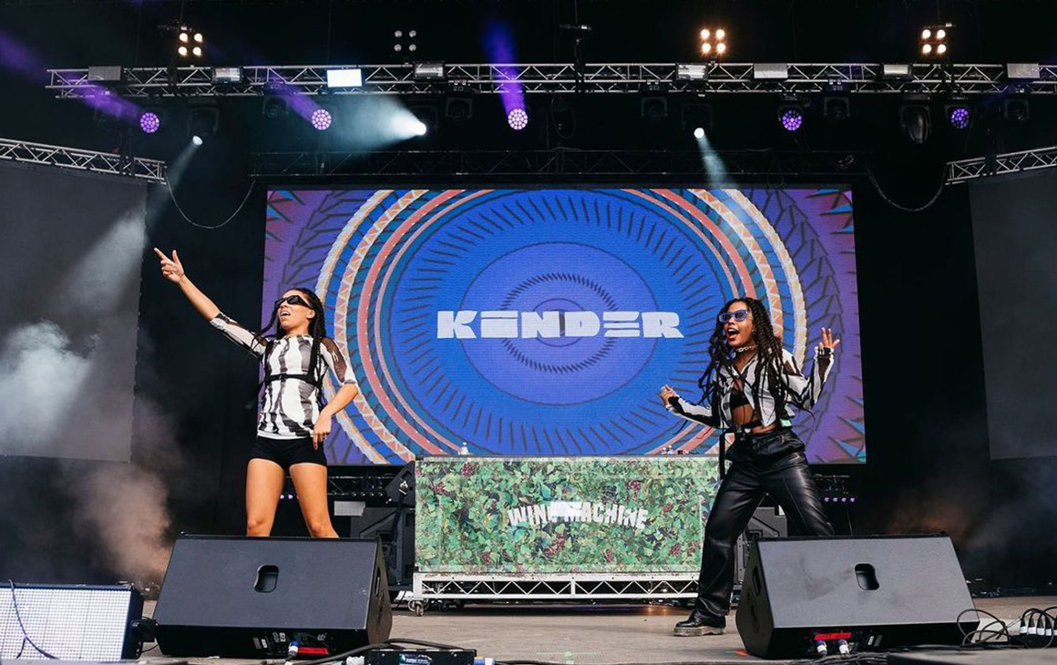Kinder dance around the stage as they perform at a festival