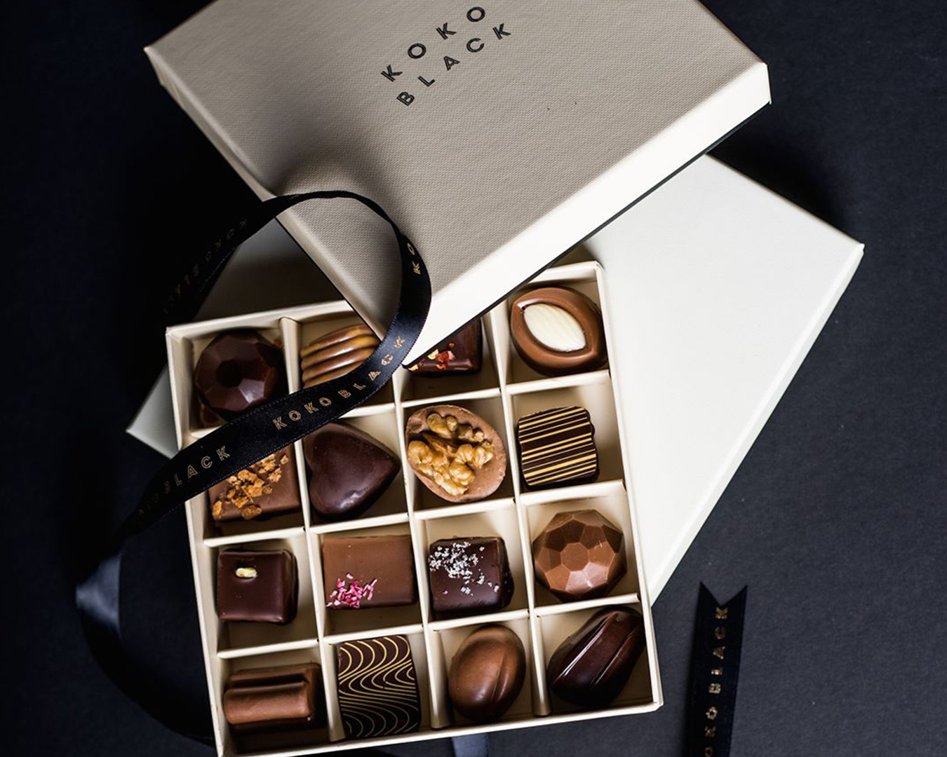 a white box lies open on a table, filled with various chocolate.