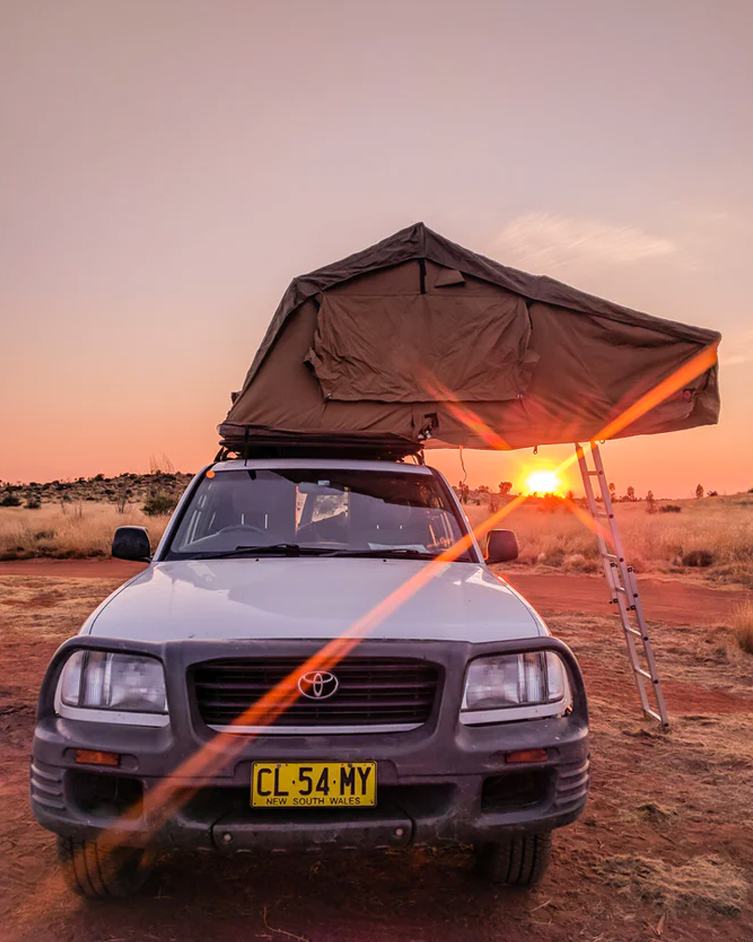 four wheel drive with overhead camping set up at sunset in Australian outback