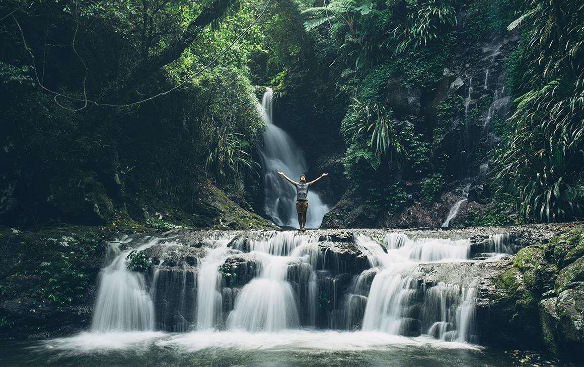 man with his hands in the air, standing on the edge of a small waterfall amongst the trees