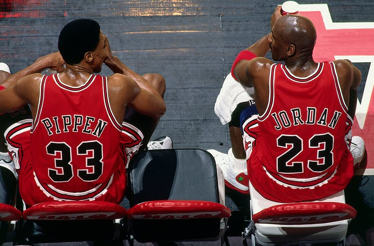 Chicago Bulls teammates Scottie Pippen and Michael Jordan sit court-side, at half-time during a game. They have their backs to the camera with their jerseys on proud display, with their heads close as they talk game play
