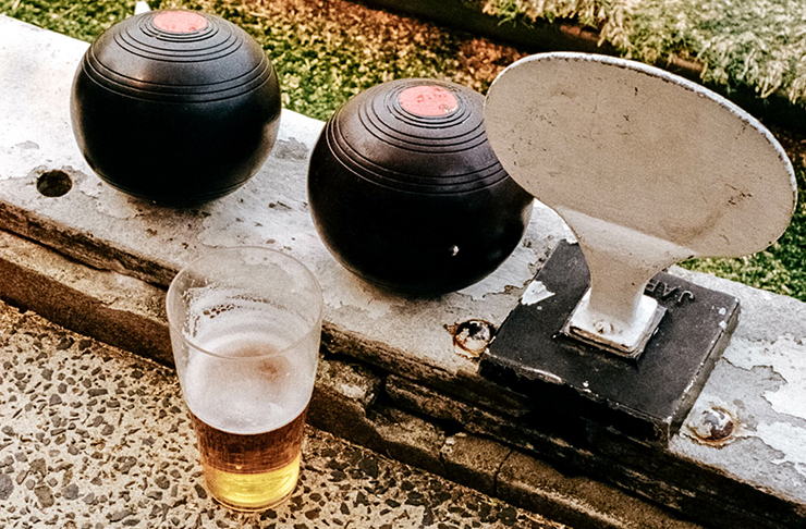 two lawn bowls and a schooner of beer