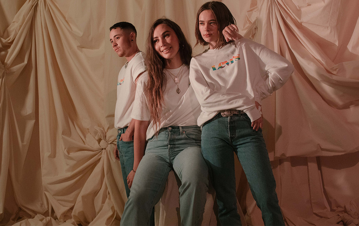 a trio model the Levi's new pride range with white jumpers and blue jeans.