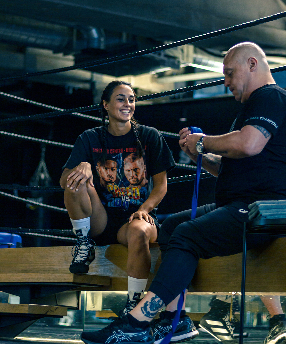 Linn Sandstrom sits on the edge of boxing ring with her trainer