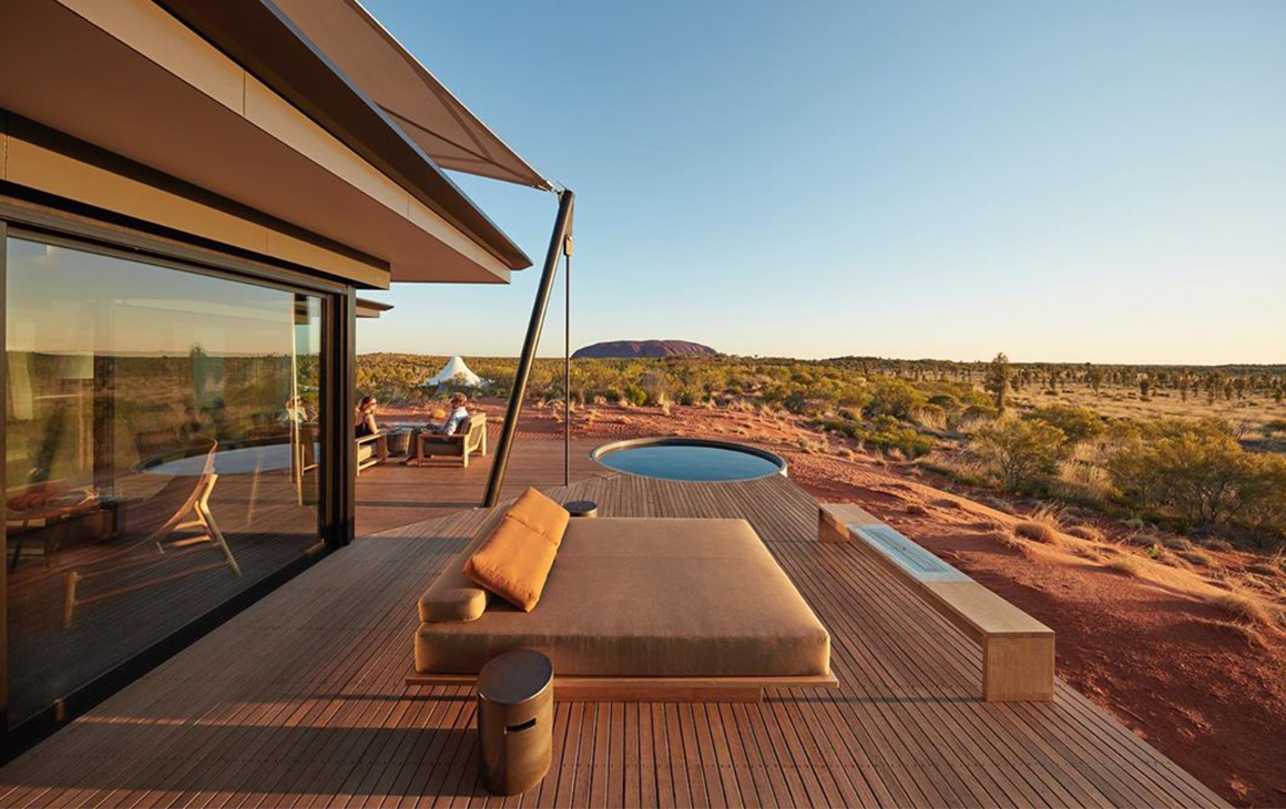The exterior of a glamping tent featuring a dip pool, day bed and Uluru in the distance.