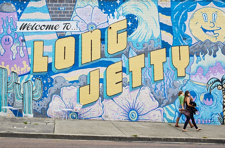 Colourful Long Jetty Mural along a brick wall with two women walking by.