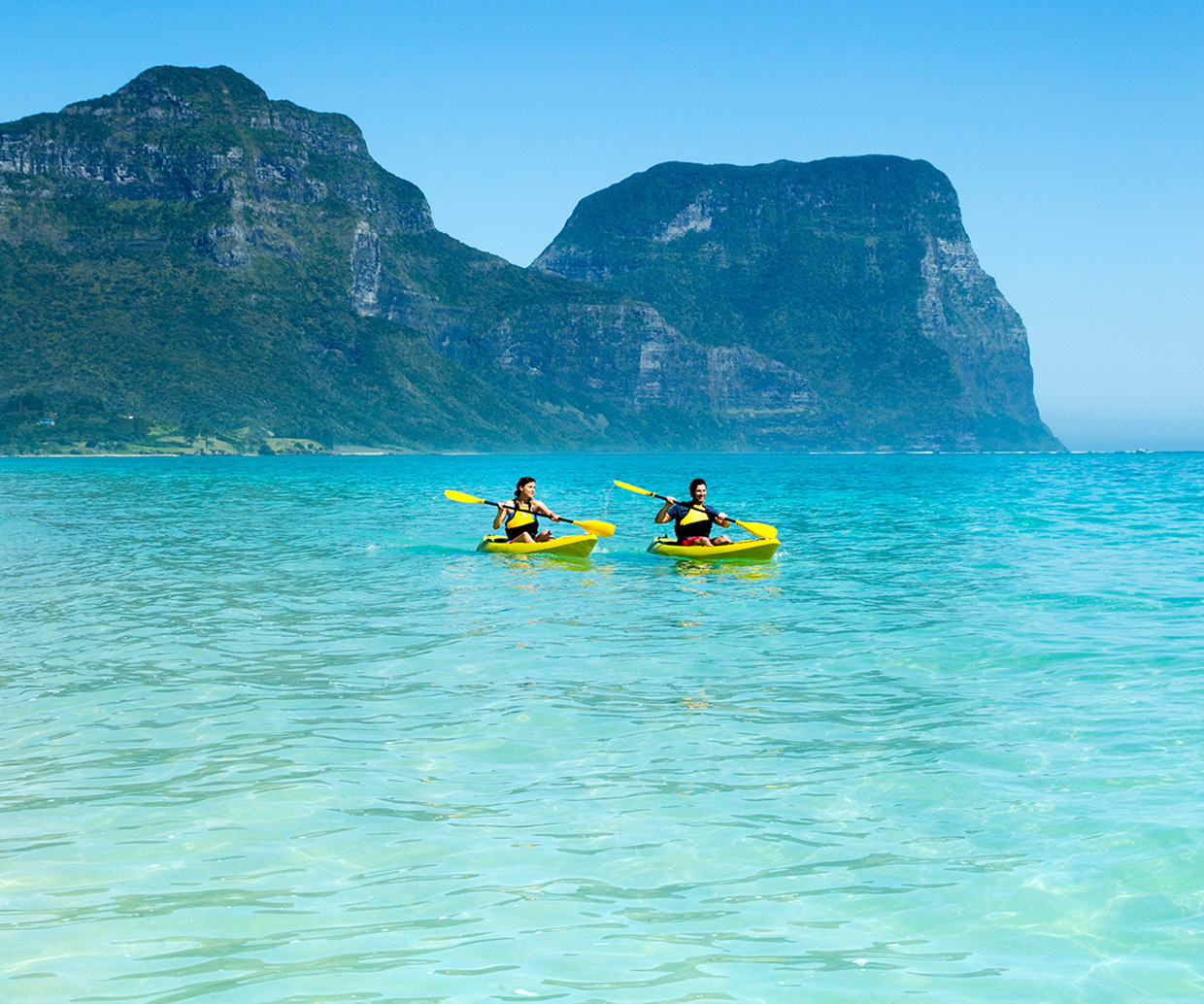 two people kayaking on crystal clear water