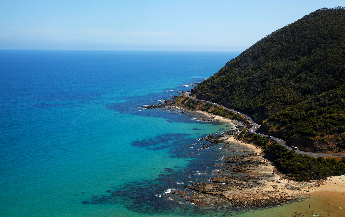 azure water edges against a rugged cliffside in Lorne.