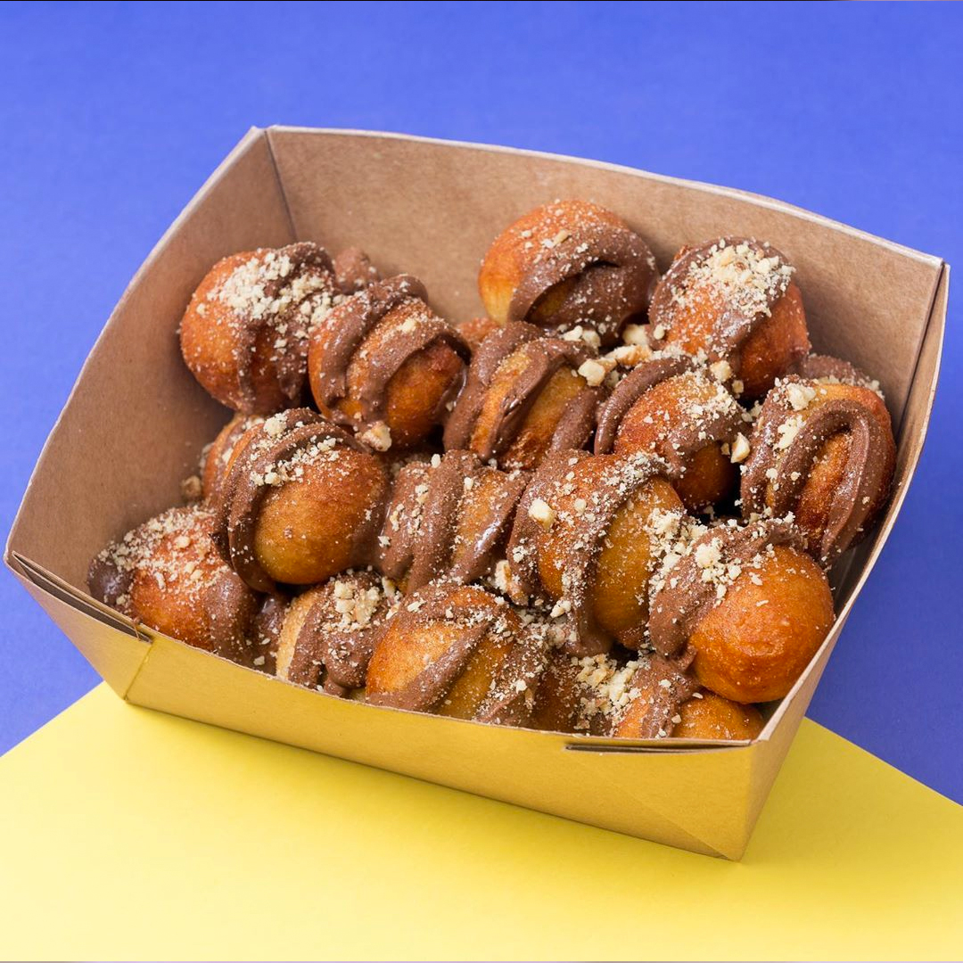 loaded loukoumades (greek doughnuts) topped with nutella drizzle and icing sugar