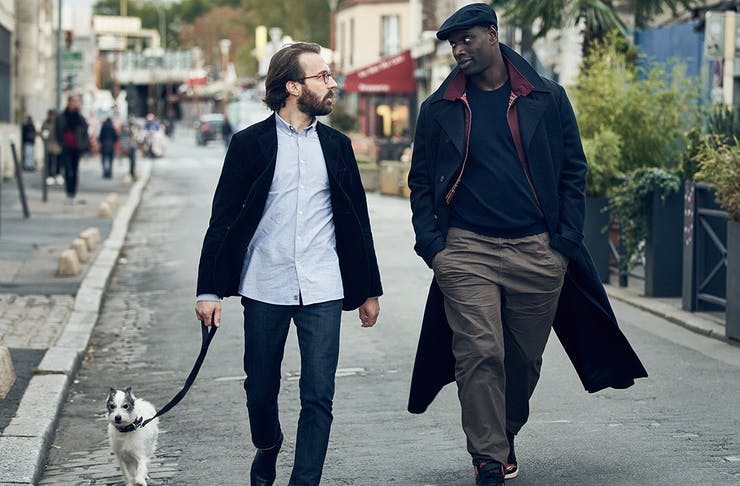 Two men, one holding a dog's leash, walk down a village street.