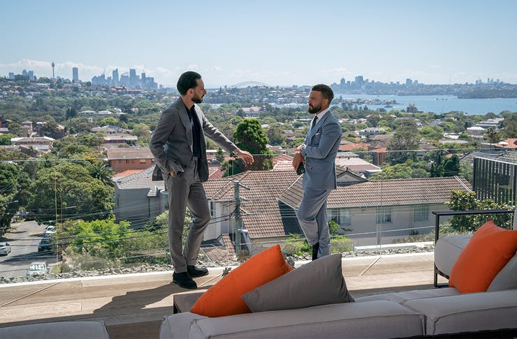 Two men in suits stand on a balcony overlooking the Sydney harbour.