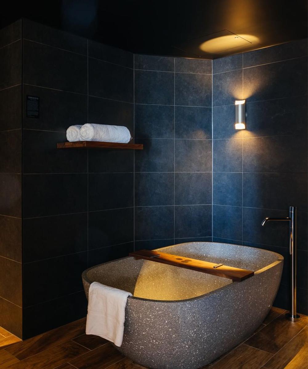 a stone bath in a black tile bathroom at MACQ 01