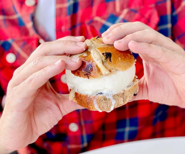 hand holding hot cross bun