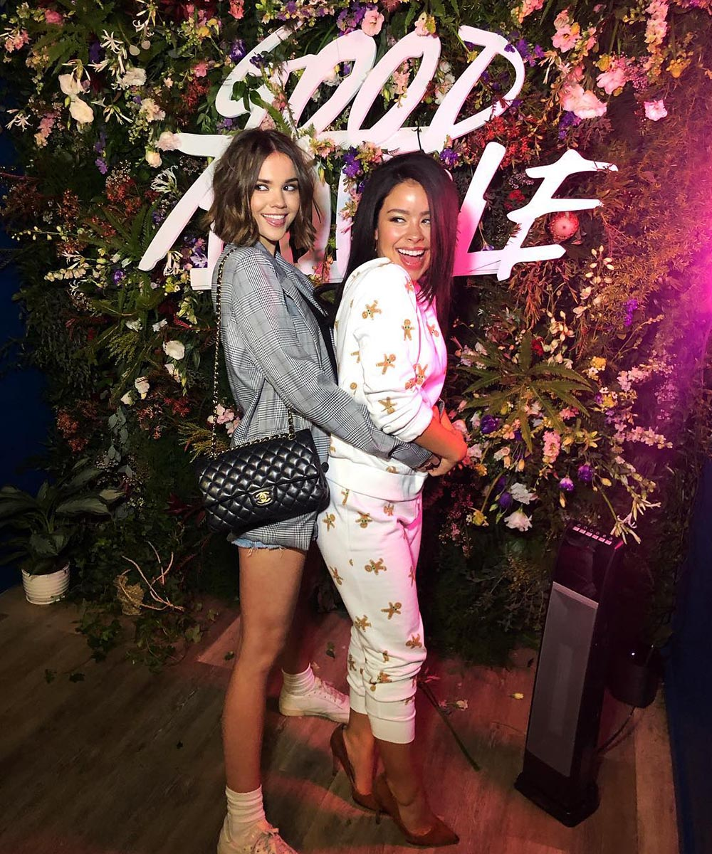 Maia Mitchell and Cierra Ramirez embrace in front of flower wall with the words Good Trouble on it.