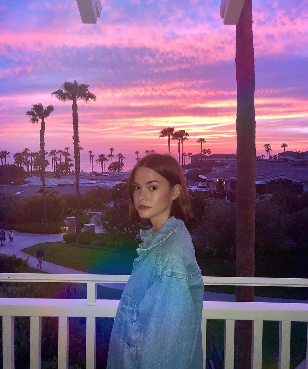 maia mitchell poses on a balcony with a stunning LA sunset behind filled with dreamy pink and dusty blues.
