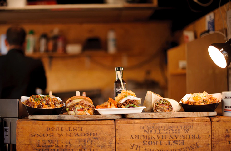 line-up of pulled pork burgers on wooden slate