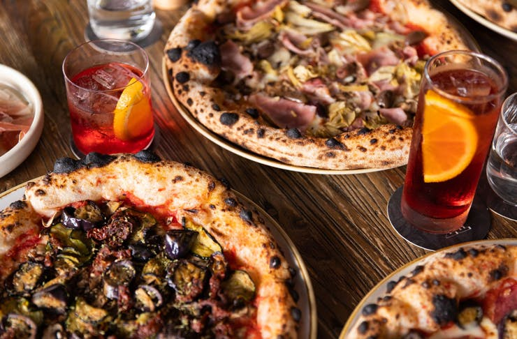 selection of pizzas on wooden table with various cocktails