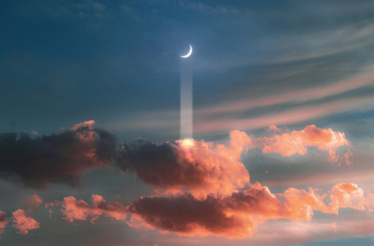 a crescent moon floats above a cluster of pink clouds.