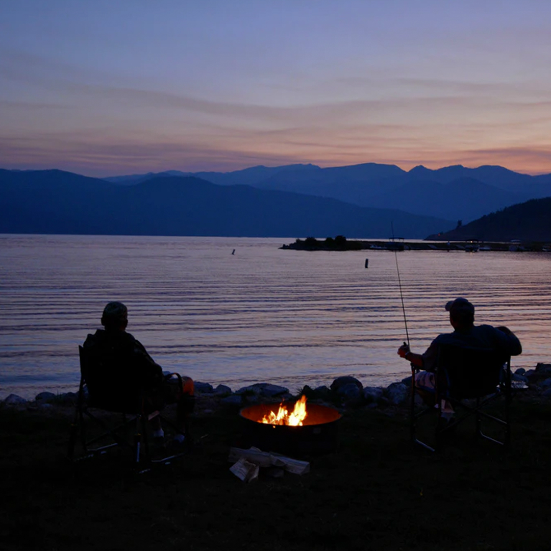 silhouette of people camping lakeside with campfire while fishing at night