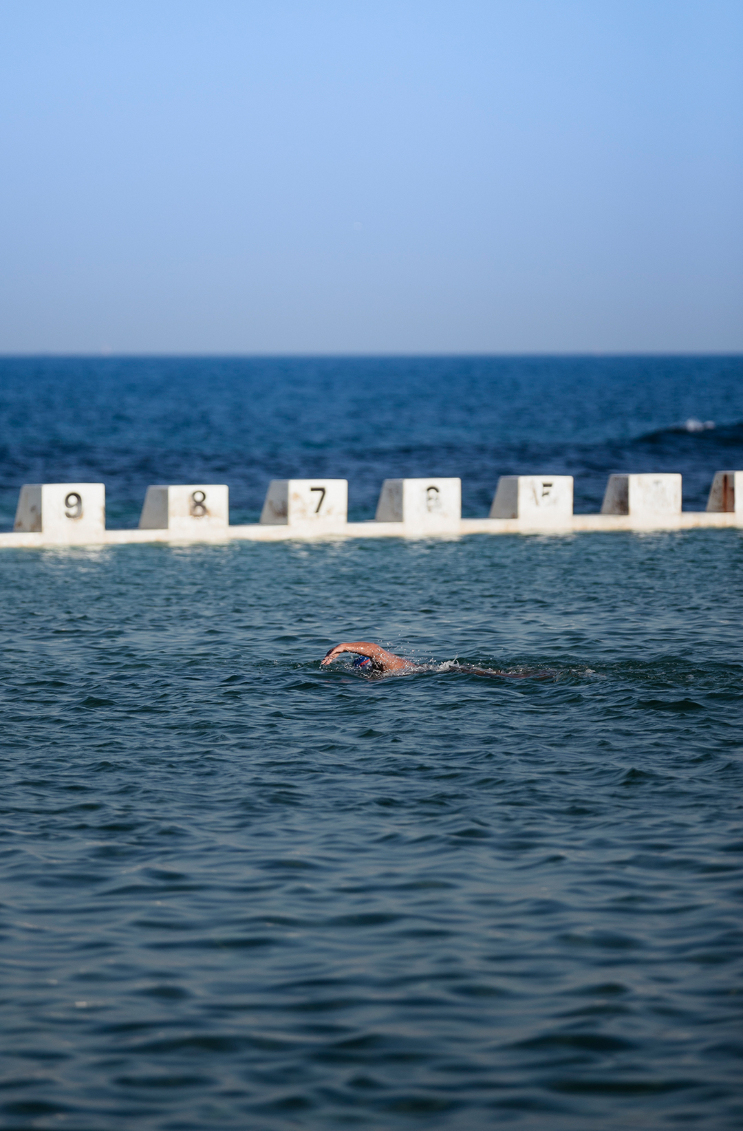 person swimming in ocean pool on clear day