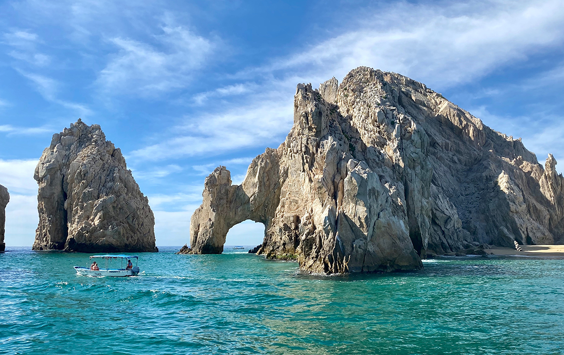 A craggy rock with a large hole in the middle juts out over the ocean in Los Cabos.