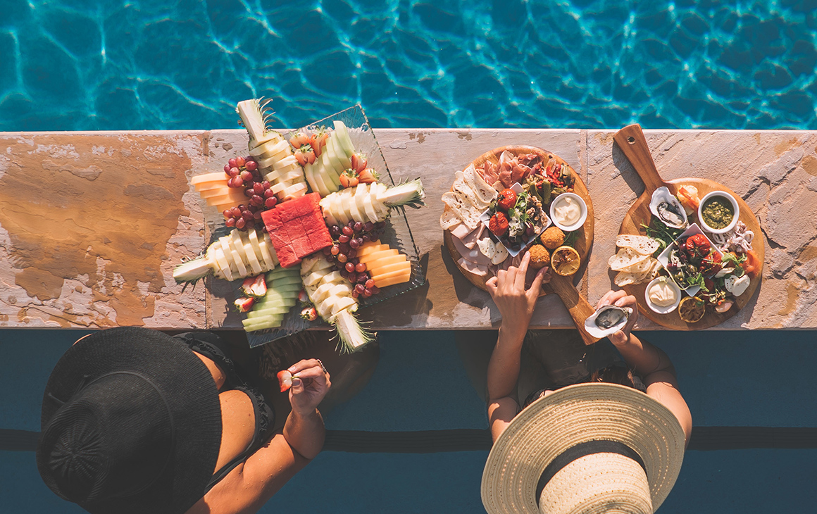 two women eat breakfast at the edge of a pool