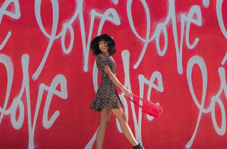 A woman smiles as she walks in front of a red wall with the word 'love' written all over it.