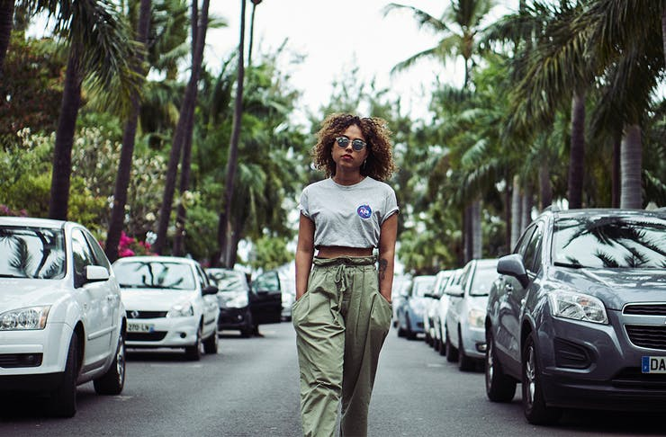 a woman, hands in her pockets, walks down a tree-lined street